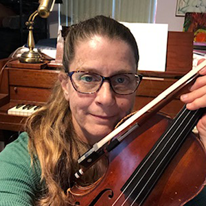 Photo of Shelley Mathews - a white woman with auburn hair and glasses holding a violin in front of a piano